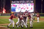 Arkansas players mob Evan Lee after he scored the winning run Friday, April 14, 2017, during the 10th inning against Georgia at Baum Stadium in Fayetteville.