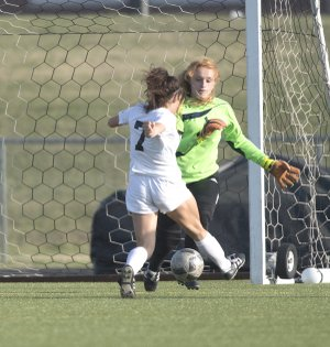 NWA Democrat-Gazette/J.T. WAMPLER Bentonville High's Angelina Diaz (7) bears down on and beats Fayetteville keeper Gracie Cape on Friday at Bentonville.