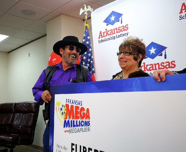 eliberto-cantu-and-his-wife-anita-smile-monday-while-holding-up-their-check-from-the-arkansas-scholarship-lottery-for-winning-the-mega-millions-jackpot