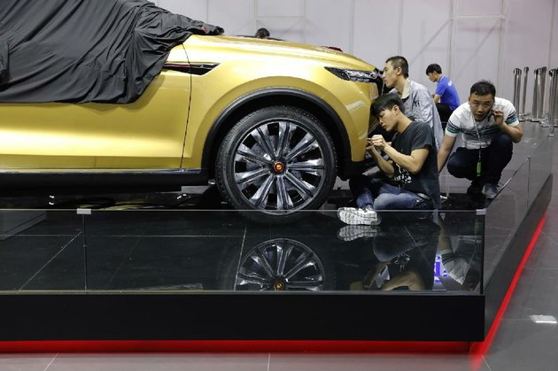 chinese-workers-prepare-for-the-shanghai-auto-show-at-the-citys-national-exhibition-and-convention-center-on-tuesday