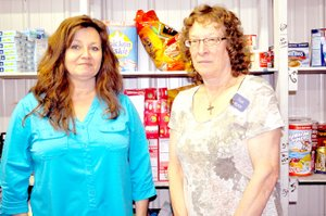 RACHEL DICKERSON/MCDONALD COUNTY PRESS Angie Martin, executive director of Crosslines of McDonald County, and Sue Willmann of Arvest Bank, are pictured at the Crosslines food pantry. Arvest recently kicked off its 1 Million Meals initiative, which will benefit Crosslines.