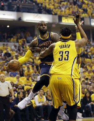 Cleveland forward LeBron James (left) wraps a pass around Indiana defender Myles Turner in the first half of Thursday night's NBA Eastern Conference playoff game. James scored 28 of his 41 points in the second half to rally the Cavaliers back from a 25-point, halftime defi cit to beat the Pacers 119-114.