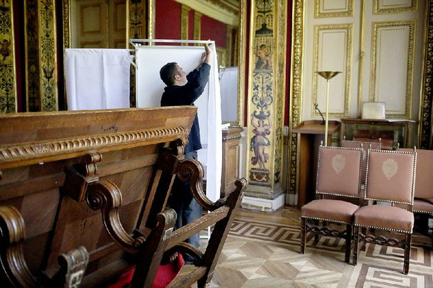 a-worker-prepares-a-polling-booth-in-paris-ahead-of-the-fi-rst-round-of-presidential-voting-in-france-that-takes-place-sunday