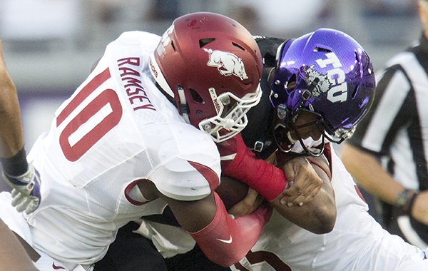 TCU junior quarterback Kenny Hill is stopped for a loss by Arkansas sophomore defensive end Randy Ramsey (left) and senior defensive linemen Jeremiah Ledbetter on Saturday, Sept. 10, 2016, at Amon G. Carter Stadium in Fort Worth, Texas.