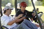 Arkansas women's golf coach Shauna Estes-Taylor (right) talks with assistant Mike Adams at the KPMG Stacy Lewis Junior All-Star Invitational at Blessings Golf Club in Fayetteville on Tuesday, June 23, 2015.