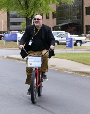 Acxiom CEO and President Scott Howe rides a bicycle between buildings earlier this month at the company's corporate headquarters in Conway. Howe said that Acxiom today reminds him of Amazon when it first began expanding its business beyond books.