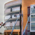 A line of construction workers in bucket lifts dot the front of the newly constructed Children's Hos...