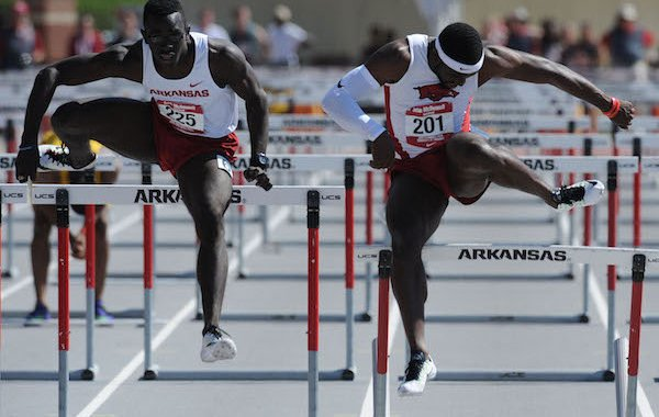 Arkansas' Davon Anderson (right) catches a hurdle Saturday, April 23, 2016, as Kemar Mowatt pulls ahead in the 110-meter hurdles during the John McDonnell Invitational at John McDonnell Field in Fayetteville.