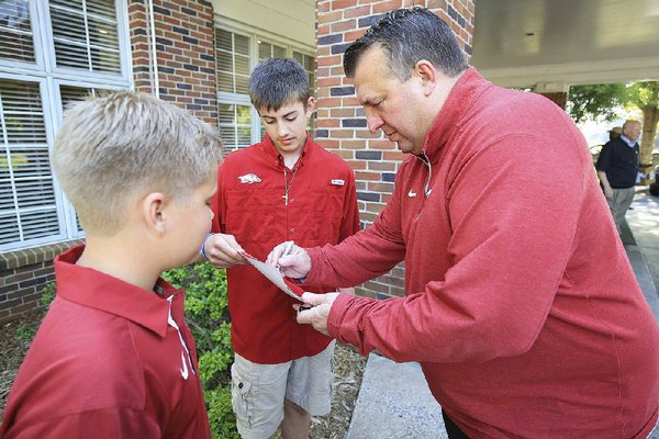 Arkansas Democrat-Gazette/STATON BREIDENTHAL --5/8/17-- Arkansas football coach Bret Bielema signs auto graphs for Will Colclasure (left), 11, and Garett Rhodes (middle), 13,  Monday night before an event at the Pine Bluff country club.