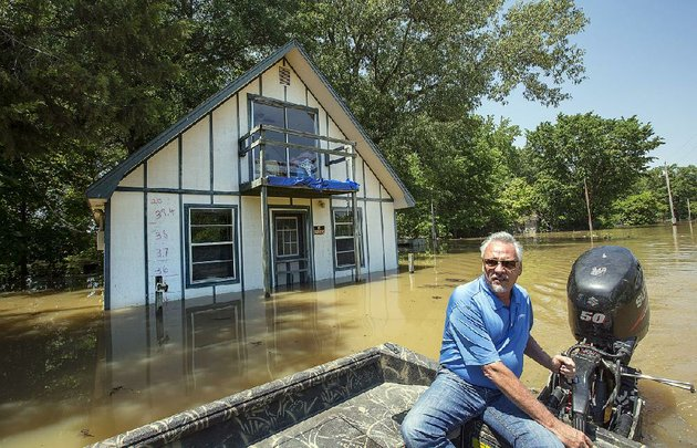 butch-rice-pilots-a-boat-monday-past-a-home-in-the-spring-lake-area-of-des-arc-where-the-water-level-has-risen-to-nearly-35-feet-4-feet-lower-than-the-record-mark-of-394-feet-set-in-2011-more-photos-are-available-online-at-arkansasonlinecomgalleries