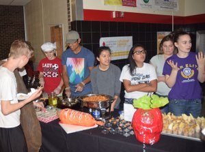 Francisco Jasso (in baseball cap) serves samples of his caliente jalapeno quesadillas to the students at McDonald County High School during lunch last week. Students in a nutrition and wellness class taught by Marie Strader developed five recipes that met federal regulations with the winning recipe to be included in next year's lunch menu.