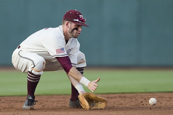 Texas A&M shortstop Austin Homan scoops up a grounder hit by Arkansas' Carson Shaddy during a college baseball game Thursday, May 18, 2017, in College Station, Texas. (Timothy Hurst/College Station Eagle via AP)