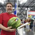 Carlos Vasquez of Springdale carries his watermelon after making the first purchase Thursday at the ...