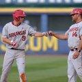Jax Biggers (9), Arkansas shortstop, fist bumps first base coach Josh Elander after reaching first i...