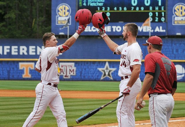 Arkansas right fielder Eric Cole is greeted at home plate by first baseman Chad Spanberger after Cole's home run in the third inning gave the R