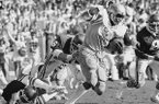 UCLAs running back James Owens, center, busts through the line for eight yards as Arkansas right tackle Dan Hampton attempts to make the tackle during second quarter action at the Fiesta Bowl, Monday, Dec. 25, 1978, Tempe, Ariz. (AP Photo/Lennox McLendon)