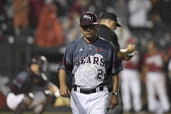 Missouri State coach Keith Guttin walks back to the bench after talking with the home plate umpire about his decision to continue the game against Arkansas after heavy rain began to fall in the 8th inning of an NCAA college baseball regional tournament game, Sunday, June 4, 2017, in Fayetteville, Ark. (AP Photo/Michael Woods)
