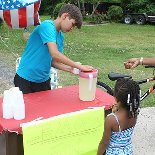 The Sentinel-Record/Richard Rasmussen HARD AT WORK: Kaleb Hayes, 14, serves some lemonade to Syncere Burton, 4, Monday at his lemonade stand outside his home in the 300 block of Woodlawn Avenue. Hayes was selling lemonade to raise money to buy a bicycle on Thursday, which prompted an outpouring from the local community, resulting in two bicycles being given to him.