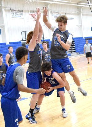 Photo by Mike Eckels Decatur's Levi Newman (center) fights his way out of a pair of Hornet blockers during the Bulldog-Hornet scrimmage game which was part of the Colcord Summer Basketball League in the gym at Colcord High School on June 6.