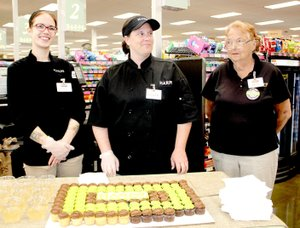 These Harps' employees — Robin Fish, Kristen Duncan and Rita Hill — welcome customers to the new Harps store in Lincoln with a cupcake and drink.