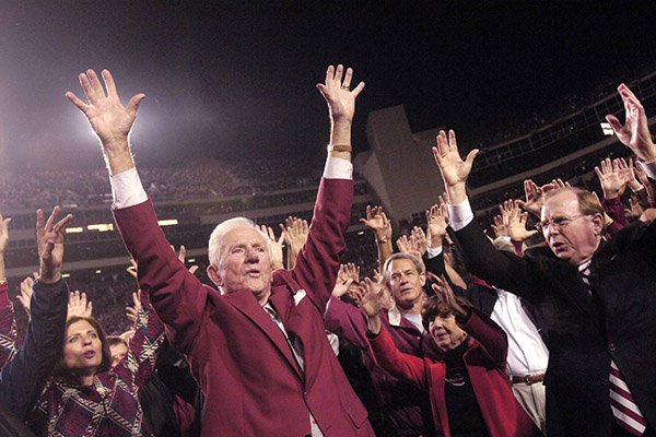 In this Nov. 3, 2007, file photo, former Arkansas coach and athletic director Frank Broyles, left, and school Chancellor John White, right, lead the school's cheer on the field at Reynolds Razorback Stadium during halftime ceremonies in a NCAAA college football game against South Carolina in Fayetteville, Ark. Broyles was retiring at the end of that year, his 50th with the school. (AP Photo/Beth Hall, File)