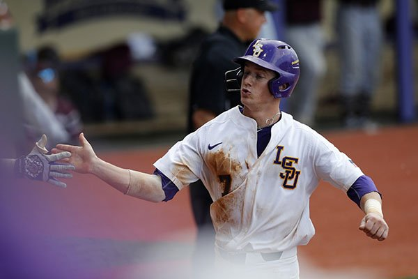 LSU's Greg Deichmann (7) is greeted after scoring on a hit by Josh Smith during the fifth inning of an NCAA college baseball tournament regional game against Texas Southern in Baton Rouge, La., Friday, June 2, 2017. LSU won 15-7. (AP Photo/Gerald Herbert)