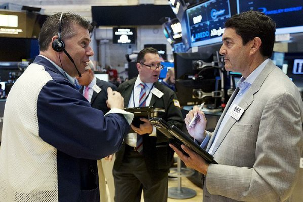 Credit AP  RICHARD DREW					Traders William Mc Inerney, and Mark Muller confer Friday on the floor of the New York Stock Exchange