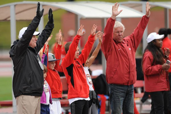 Arkansas coaches Chris Bucknam (left) and Lance Harter call the Hogs Saturday, April 22, 2017, with winners of the Fastest Kid in Fayetteville competition during the John McDonnell Invitational at John McDonnell Field in Fayetteville.