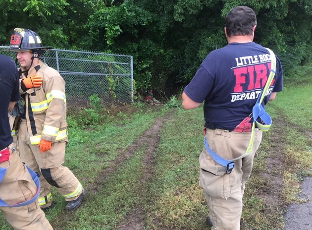 little-rock-fire-department-officials-stand-at-the-scene-of-an-accident-where-a-car-ran-off-a-roadway-and-into-a-creek-monday-morning