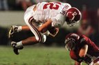 Alabama quarterback John David Phillips (12) is up-ended by Arkansas defensive tackle Melvin Bradley during the third quarter of the Southeastern Conference game in Fayetteville, Ark., on Saturday, Sept. 26, 1998. Arkansas beat No. 22 Alabama 42-6. (AP Photo/Beau Rogers)