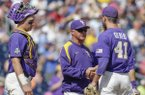 LSU pitcher Caleb Gilbert, right, receives a handshake from coach Paul Mainieri, center, with catcher Michael Papierski (2) watching after holding No. 1 national seed Oregon State to two hits in 7 1/3 innings in an NCAA College World Series baseball elimination game in Omaha, Neb., Saturday, June 24, 2017. (AP Photo/Nati Harnik)