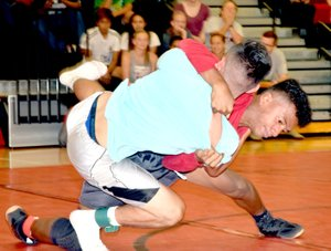 Photo by Rick Peck Trent Alik throws Uriel Lazaro to his back on the way to a pin in the 126-pound weight class at the MCHS summer school intramural wrestling tournament.
