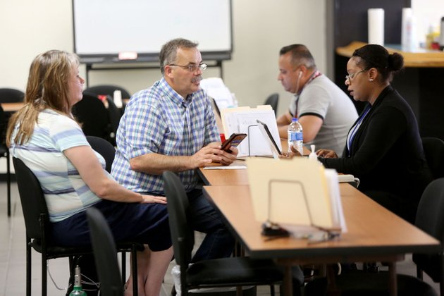 aslin-davila-from-right-applicant-service-program-specialist-assists-darrell-and-shelley-barron-of-washington-county-friday-at-the-federal-emergency-management-agency-recovery-center-located-in-the-fayetteville-executive-airport-terminal-building-at-drake-field-the-center-is-designed-to-provide-face-to-face-recovery-assistance-to-residents-with-needs-after-flood-damage-earlier-this-year