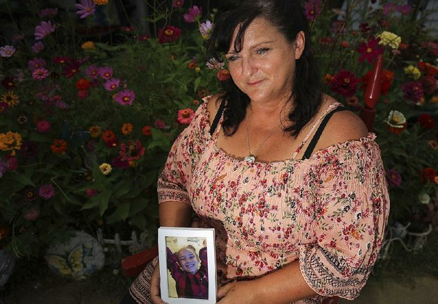 brenda-wezowicz-holds-a-photo-of-her-granddaughter-karma-wezowicz-as-she-sits-in-front-of-the-butterfly-garden-they-had-planned-together