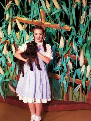 Katherine Yacko plays Dorothy and Archie plays Toto in The Wizard of Oz at Murry's Dinner Playhouse.
