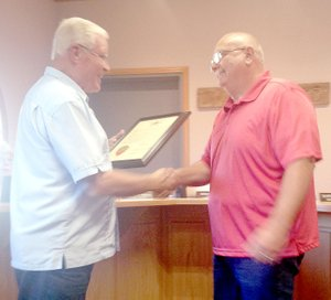 Sally Carroll/McDonald County Press State Rep. Bill Lant, left, presents Pineville Mayor and County Emergency Management Agency Director Gregg Sweeten with a resolution honoring him for his dedication to community.