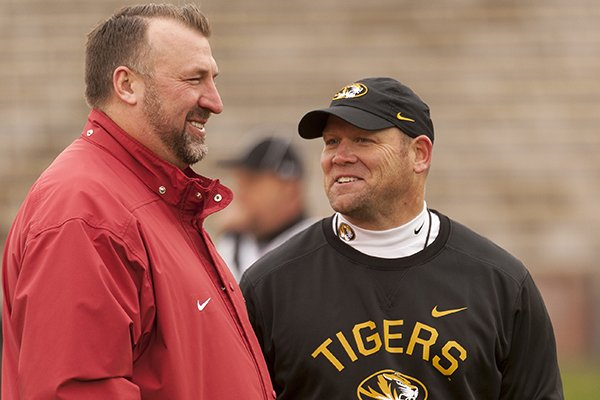 Missouri head coach Barry Odom, right, laughs with Arkansas head coach Bret Bielema, left, before the start of an NCAA college football game Friday, Nov. 25, 2016, in Columbia, Mo. (AP Photo/L.G. Patterson)