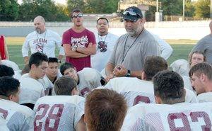 Graham Thomas/Siloam Sunday Siloam Springs football coach Bryan Ross speaks to the Panthers after hosting a football team camp with Gravette and Farmington on Thursday at Panther Stadium.