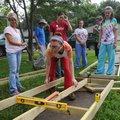 NWA Democrat-Gazette/FLIP PUTTHOFF  Camryn Clarke (center) checks the level of a wheelchair ramp Tu...