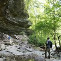 Isaac Ogle (right) and his wife, Jennifer, explore a bluff shelter along a spring-fed creek Sunday i...