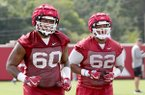 Arkansas offensive linemen Brian Wallace (60) and Johnny Gibson (62) run during practice Thursday, July 27, 2017, in Fayetteville.