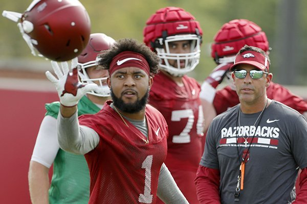 Arkansas receiver Jared Cornelius catches his helmet during practice Thursday, July 27, 2017, in Fayetteville.