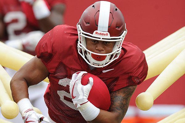 Arkansas running back Devwah Whaley carries the ball through a practice device Tuesday, Aug. 1, 2017, during practice at the university's practice field in Fayetteville.