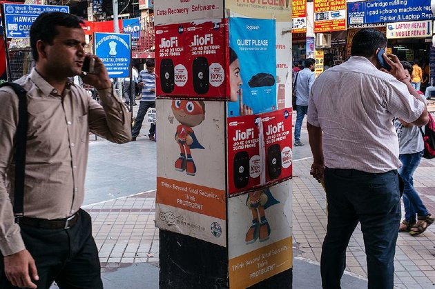 pedestrians-use-smartphones-near-advertising-for-the-jio-mobile-network-at-the-nehru-place-it-market-in-new-delhi-in-may