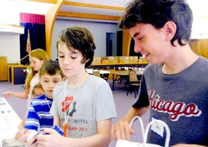 Lynn Atkins/The Weekly Vista Miles Davis, Miles Hyman, Wesley Tribble and Mykenna Morgan fill bags for residents of Brookfield Assisted Living during the Creative Kids Make and Share It summer camp at the Presbyterian Church of Bella Vista last week. Each day, the campers made an item and donated it to a group in Bella Vista.