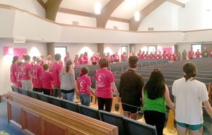 Volunteers with the Farmington Back to School Bonanza join hands in a large circle to pray before the first families come into the church. About 200 people helped with the Bonanza this year.