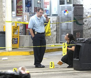 The Sentinel-Record/Richard Rasmussen CRIME SCENE: Hot Springs police Detective Scott Lampinen, left, and crime scene investigator Jennifer Brizzo work the scene of a fatal shooting late Monday at the Valero gas station, 1201 Central Ave. The victim was later identified as Derek A. Duvall, 29, of Hot Springs, who was shot once in the chest.