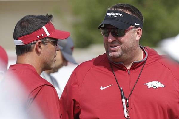 Arkansas coach Bret Bielema, right, talks with offensive coordinator Dan Enos during a practice Tuesday, Aug. 1, 2017, in Fayetteville.