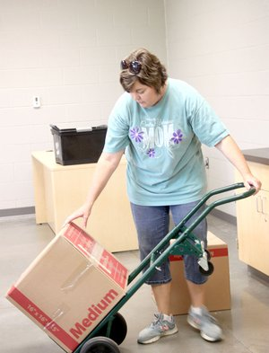 Belyn Rodgers, who teaches oral communications and AP Language and Composition, moves in boxes of books to her new classroom at Farmington High School.