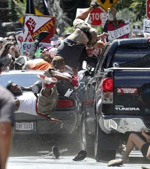 A car sends people flying Saturday as it plows into a crowd after a protest against white nationalists in Charlottesville, Va. The driver was arrested, officials said.